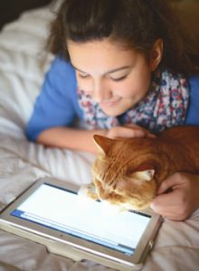 Girl and cat looking at a tablet